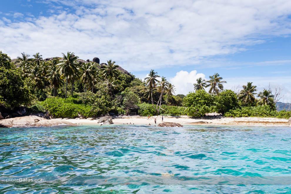 Widok z łodzi motorowej na plażę na wyspie Coco i kilkoro turystów